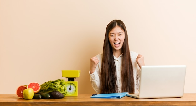 Donna cinese del giovane dietista che lavora con il suo computer portatile che incoraggia spensierato ed eccitato. concetto di vittoria.