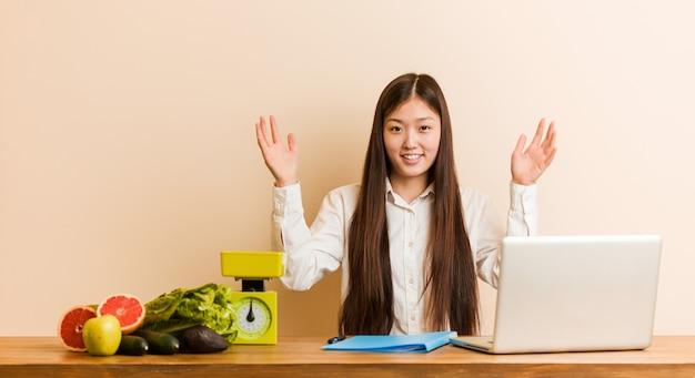 Donna cinese del giovane dietista che lavora con il suo computer portatile che riceve una sorpresa piacevole