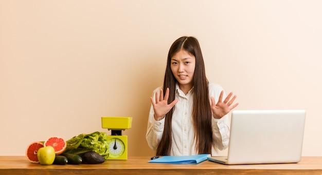 Donna cinese del giovane dietista che lavora con il suo computer portatile che rifiuta qualcuno che mostra un gesto di disgusto.