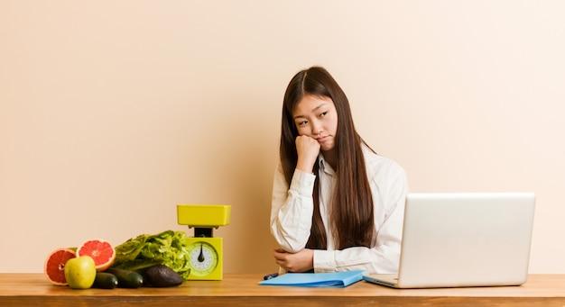 Donna cinese del giovane dietista che lavora con il suo computer portatile che si sente triste e pensieroso, esaminando lo spazio della copia.