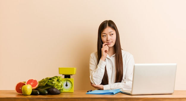 Donna cinese del giovane dietista che lavora con il suo computer portatile rilassato pensando a qualcosa che esamina uno spazio della copia.