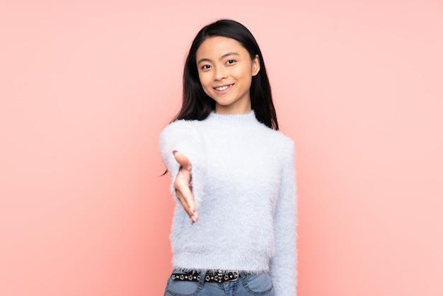 Donna cinese dell'adolescente isolata sul rosa