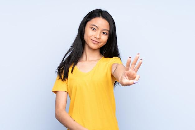 Donna cinese dell'adolescente isolata sulla parete blu felice e contando tre con le dita