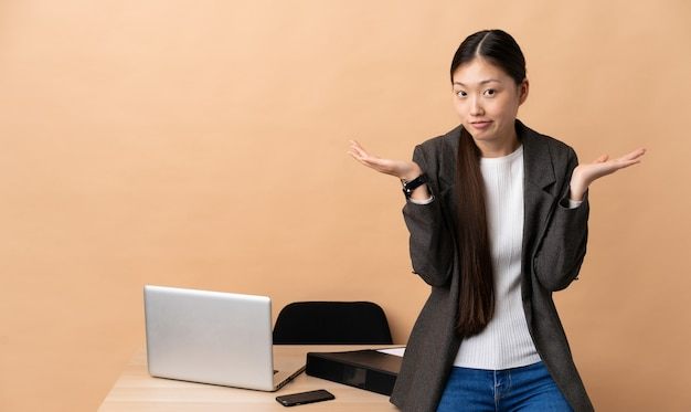 Donna cinese di affari nel suo posto di lavoro che ha dubbi mentre solleva le mani