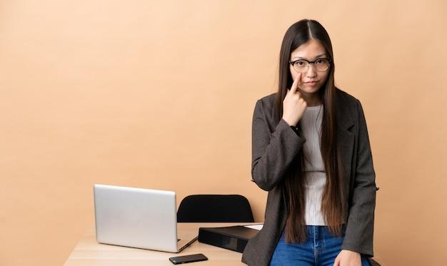 Donna cinese di affari nel suo posto di lavoro che mostra qualcosa