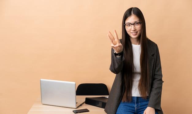 Donna cinese di affari nel suo posto di lavoro felice e contando tre con le dita