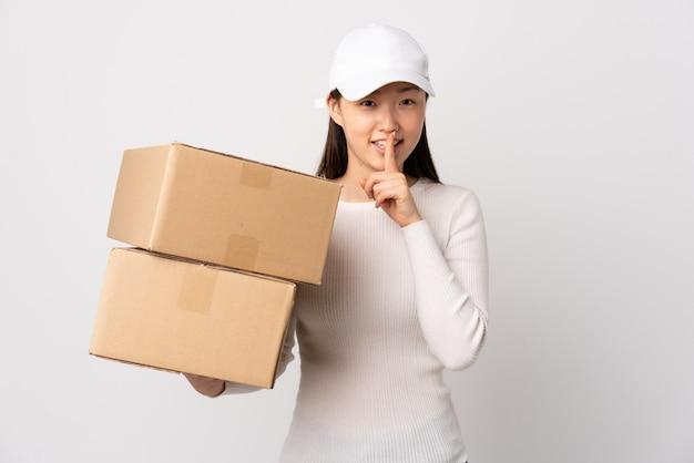 Donna cinese di giovane consegna sopra la parete bianca che fa gesto di silenzio