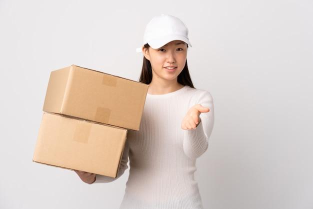 Donna cinese di giovane consegna sopra la stretta di mano bianca isolata della parete dopo il buon affare