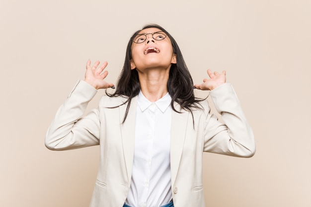 Donna cinese di giovani affari che grida al cielo, guardante su, frustrato.