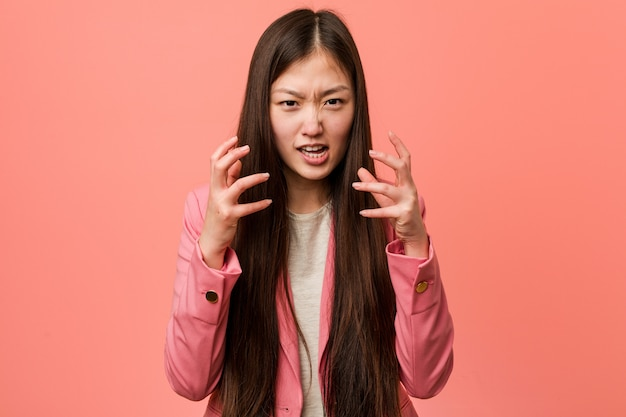 Donna cinese di giovani affari che indossa turbamento del vestito rosa che grida con le mani tese.