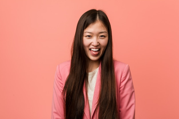 Donna cinese di giovani affari che indossa vestito rosa divertente e amichevole che lo attacca fuori lingua.