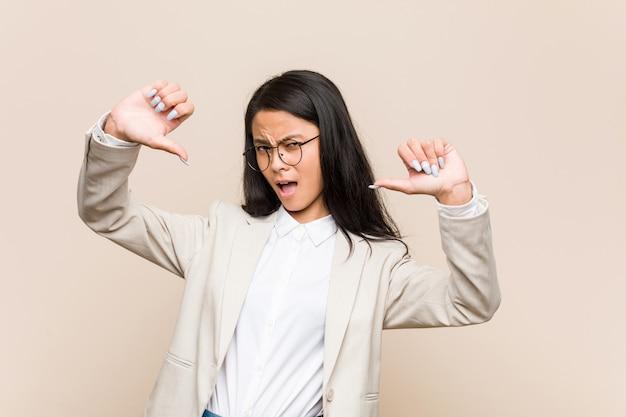 Donna cinese di giovani affari che mostra pollice giù e che esprime antipatia