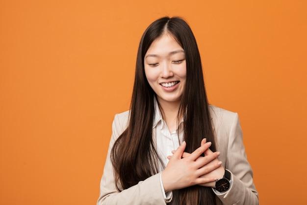 Donna cinese di giovani affari che ride tenendo le mani sul cuore, concetto di felicità.