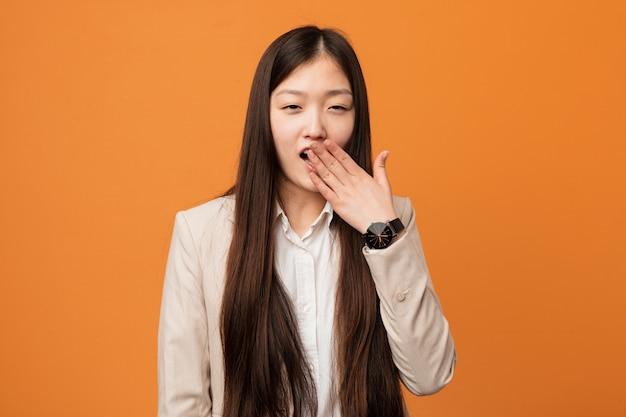 Donna cinese di giovani affari che sbadiglia mostrando una bocca stanca della copertura di gesto con lui mano.