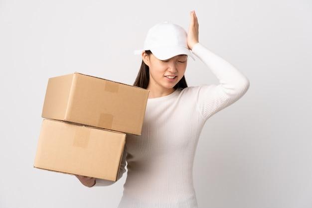 Donna cinese giovane consegna sul muro bianco con dubbi con espressione del viso confuso