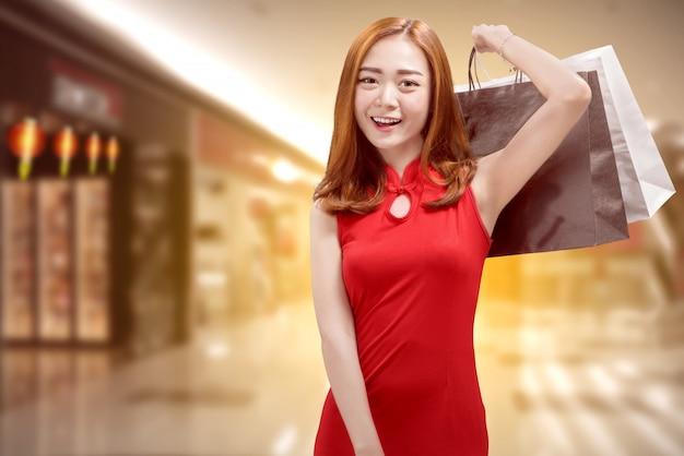 Donna cinese graziosa in vestito tradizionale che porta i sacchetti della spesa