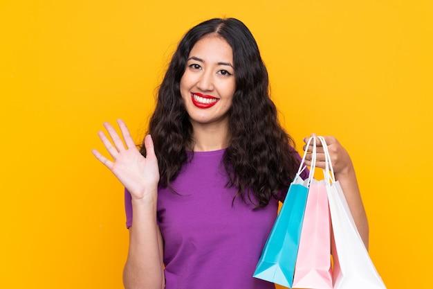 Donna cinese spagnola con il sacchetto della spesa che saluta con la mano con l'espressione felice