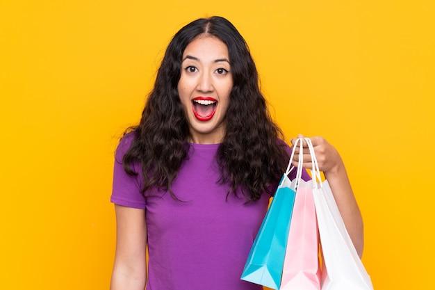 Donna cinese spagnola con il sacchetto della spesa sopra la parete isolata con espressione facciale sorpresa e colpita