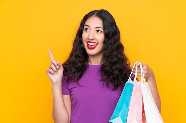 Donna cinese spagnola con la borsa della spesa che intende realizzare la soluzione sollevando un dito