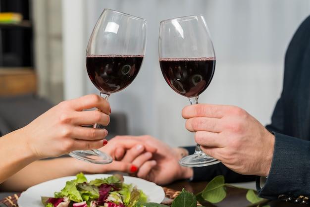 Donna clanging bicchieri di vino con l'uomo al tavolo con piastra