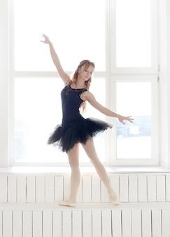 Donna classica della ballerina in vestito nero che si esercita per il cigno nero