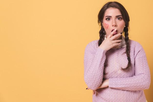 Donna colpita che posa mentre coprendo la sua bocca