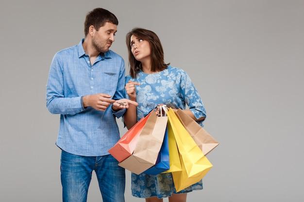 Donna con acquisti, uomo che tiene gli ultimi soldi sul muro grigio