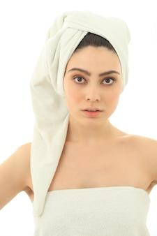 Donna con asciugamano sulla testa e sul corpo dopo la doccia