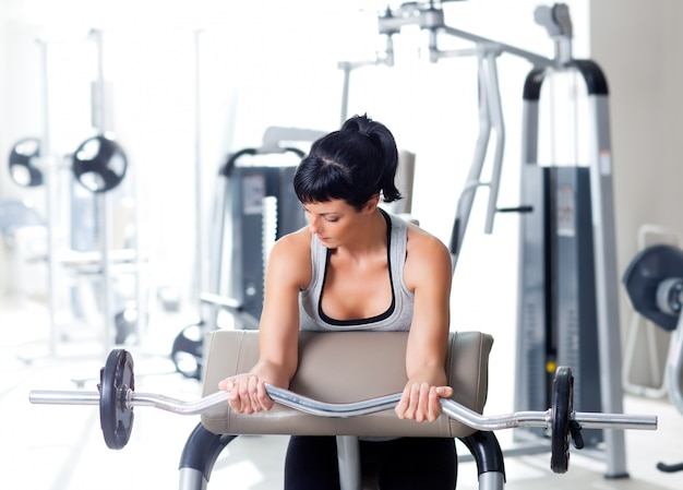 Donna con attrezzature per l'allenamento con i pesi in palestra sportiva