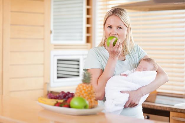 Donna con bambino in braccio a mangiare una mela