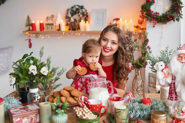Donna con bambino in cucina decorato per natale.