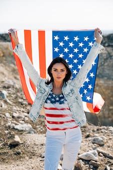 Donna con bandiera americana guardando la fotocamera