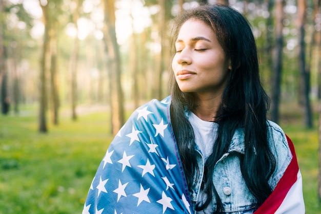 Donna con bandiera americana nel parco