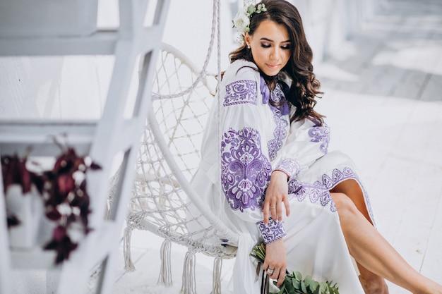 Donna con bel vestito bianco e bouquet di fiori
