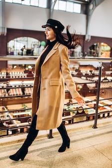 Donna con berretto in pelle nera, cappotto e stivali