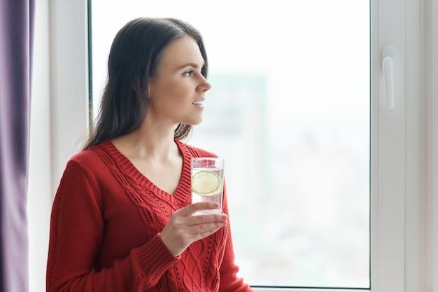Donna con bicchiere d'acqua con calce