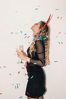Donna con bicchiere di champagne sotto lustrini