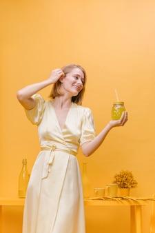 Donna con bicchiere di limonata in una scena gialla