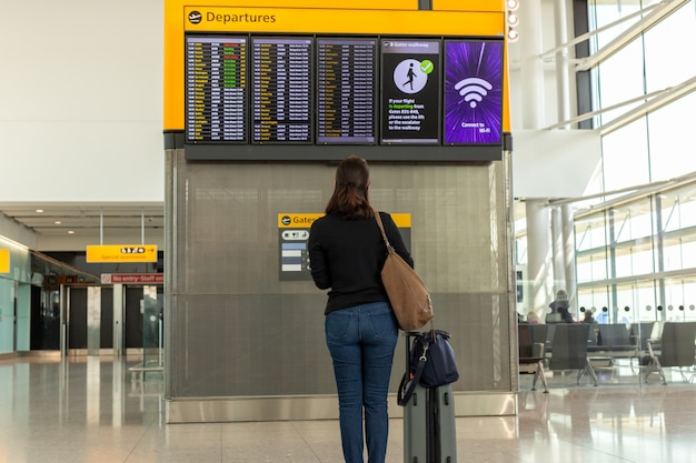 Donna con borsa a tracolla e bagagli guardando orario di volo in aeroporto internazionale