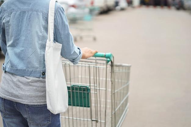Donna con borsa in tessuto per fare shopping al grande magazzino