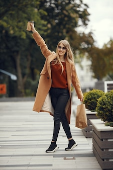 Donna con borse della spesa in una città estiva