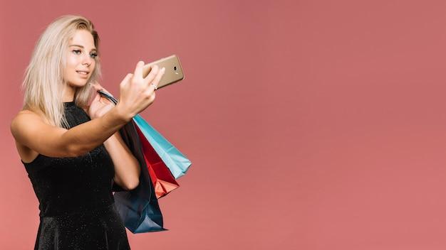 Donna con borse della spesa prendendo selfie