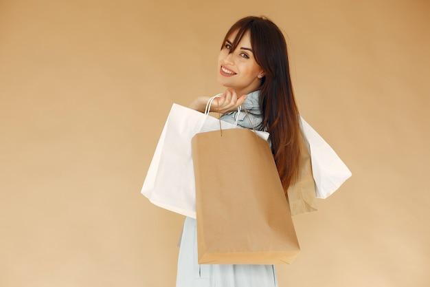 Donna con borse della spesa. signora su una parete beige. donna in una giacca blu.
