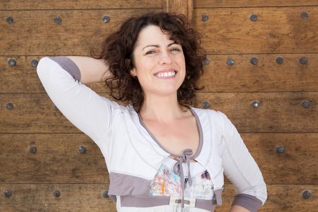 Donna con braccio alzato, sorridente con i denti in un parco e guardando la fotocamera