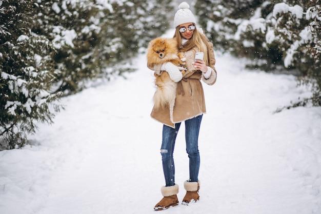 Donna con cane e telefono in inverno