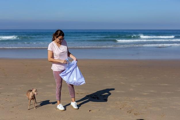 Donna con cane raccogliendo rifiuti e materie plastiche che puliscono la spiaggia