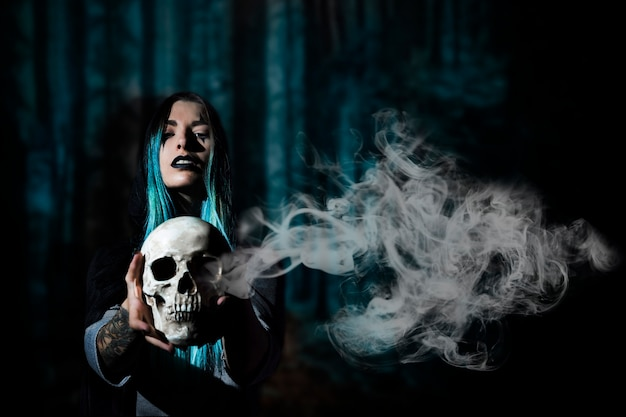 Donna con capelli blu che tengono un cranio con fumo