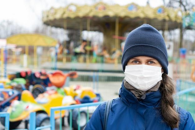 Donna con capelli castani che indossa maschera medica per il viso a causa dell'inquinamento atmosferico