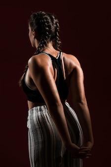 Donna con capelli lunghi nel fondo scuro da dietro il colpo