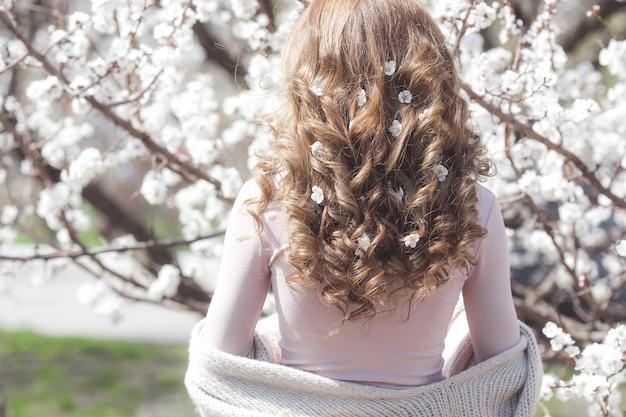 Donna con capelli ricci all'aperto sul fondo della molla. irriconoscibile signora con capelli biondi e lunghi e sani. primo piano di taglio di capelli della ragazza ancora